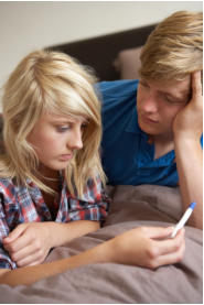 young teenage boy and girl looking at a positive pregnancy test